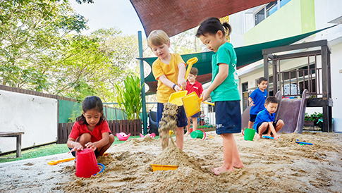 Early Years students playing together in the covered sand pit with shovels and buckets.